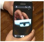휴대폰의 카메라 기능을 사용하여 리모컨의 송신부를 촬영하는 표현입니다.